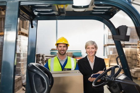 forklift driver: Warehouse manager smiling at camera with forklift driver in a large warehouse