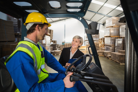 forklift driver: Warehouse manager talking with forklift driver in a large warehouse
