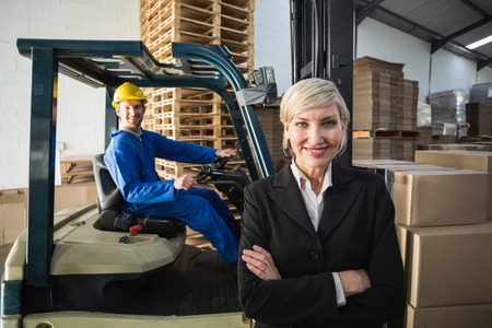 Smiling warehouse manager standing with arms crossed in a large warehouse photo
