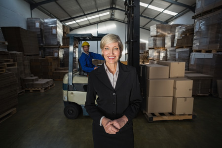 Manager standing in front of her employee in a large warehouse photo
