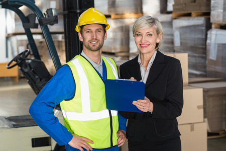 Forklift driver and his manager smiling at camera in a large warehouse photo