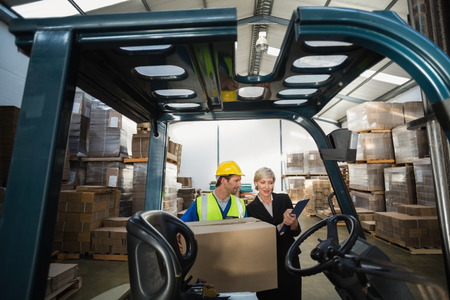 Warehouse manager talking with forklift driver in a large warehouse photo