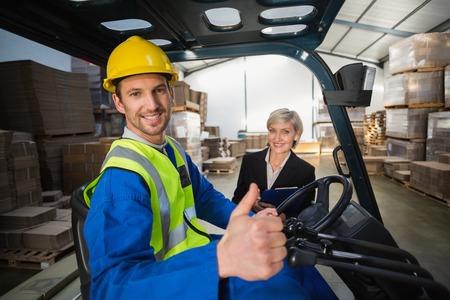 Warehouse werknemer en zijn manager lachend naar de camera in een groot magazijn Stockfoto