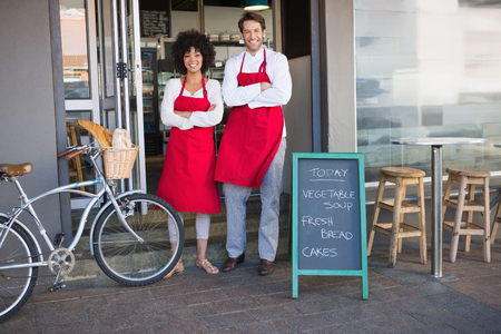 restaurant industry: Smiling colleagues in red apron with arms crossed at the bakery Stock Photo