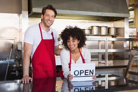 Lächelnde Mitarbeiter posiert mit geöffnetem Zeichen in der Bäckerei Standard-Bild