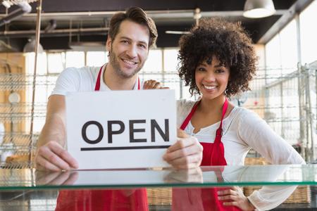 Quipe souriante posant derrière le comptoir avec signe ouvert à la boulangerie Banque d'images - 46212604