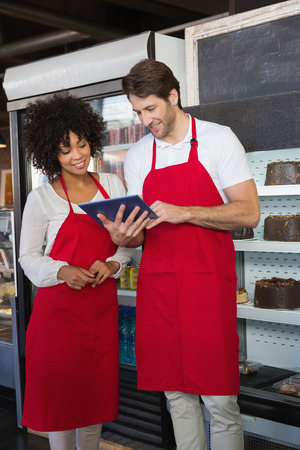 Smiling colleagues in red apron using tablet together at the bakery photo