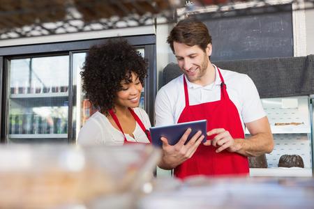 mesero: Colegas en delantal rojo que usa la tableta en la panader�a