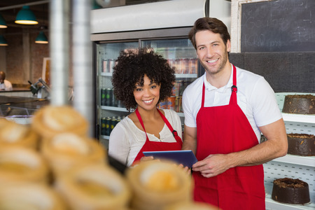 Smiling colleagues holding tablet pc at the bakery photo