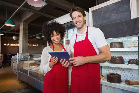 obrero trabajando: Compa�eros de trabajo felices en delantal rojo que sostienen la tablilla en la panader�a Foto de archivo