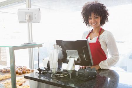 Beautiful waitress posing behind the counter at the bakery