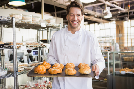 negocios comida: Panadero Alegre celebración de la bandeja de pan en la panadería Foto de archivo