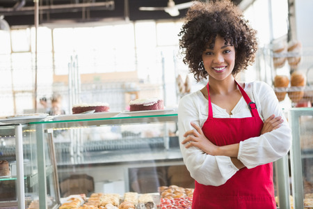mandil: Empleado bonita que presenta con los brazos cruzados en la panader�a