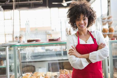 Mooie werknemer die met gekruiste armen in de bakkerij Stockfoto