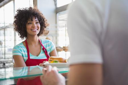 bocadillo: Camarera bonita que da s�ndwich de cliente en la panader�a Foto de archivo