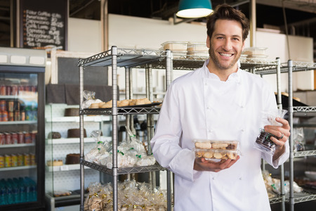 food and drink industry: Cheerful baker holding coffee house and food at the bakery Stock Photo