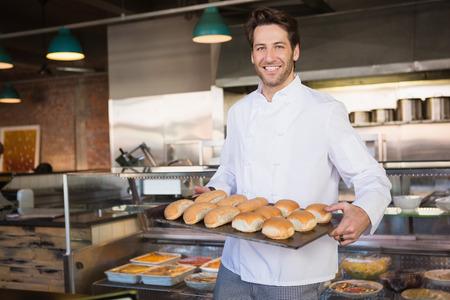 Gl�cklicher B�cker zeigt Tablett mit Brot in der B�ckerei