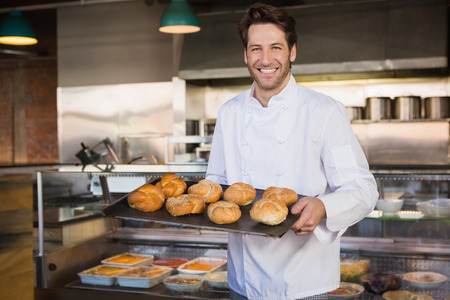bakery bread: Portrait of smiling baker holding tray with bread at the bakery Stock Photo