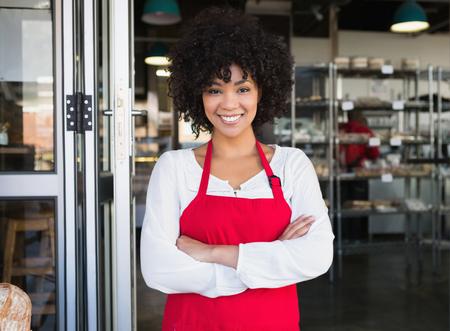 Docela serveru v červené zástěře s rukama zkříženýma v pekárně Reklamní fotografie
