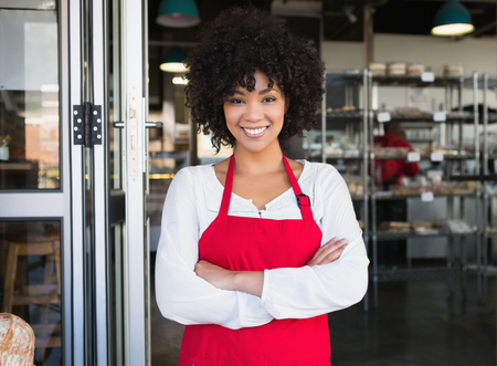 Pretty server in red apron with arms crossed at the bakery