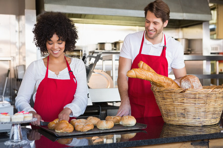 Cheerful colleagues posing with bread at the bakery