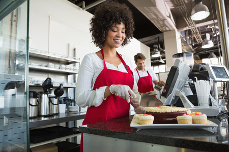 Beautiful waitress in red apron slicing cake at the bakery Standard-Bild