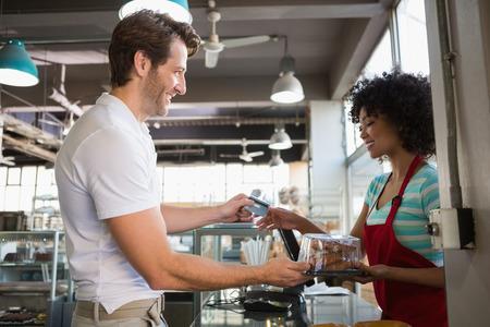 Sonreír cliente que paga con tarjeta de crédito en la panadería