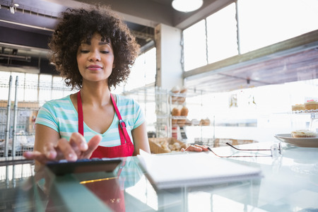calculator: Smiling employee using calculator on counter at the bakery