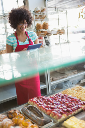 Smiling waitress using tablet pc at the bakery photo