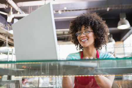restaurant industry: Smiling waitress with glasses using laptop at the bakery
