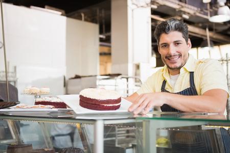 red velvet: Smiling worker showing red velvet at the bakery Stock Photo