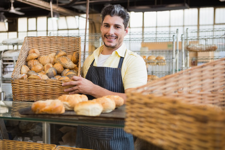 pastry shop: Portrait of happy worker holding basket of bread at the bakery Stock Photo