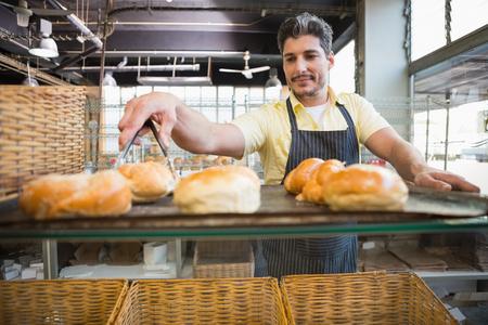 worker: Camarero sonriente de tomar pan con pinzas en la panadería