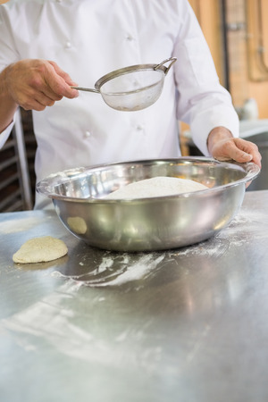 proving: Baker working with sieve and bowl in the kitchen of the bakery Stock Photo