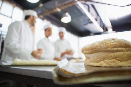 baker: Fresh bread with bakers behind him in the kitchen of the bakery Stock Photo