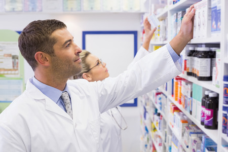 Personas de farmacéuticos mirando medicina en la farmacia del hospital Foto de archivo