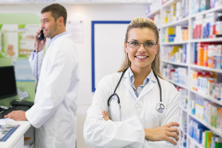 pharmacy: Pharmacist smiling with pharmacist behind on the phone at the hospital pharmacy Stock Photo
