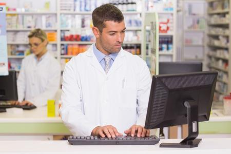 drugstore: Concéntrese farmacéutico usa el ordenador en la farmacia del hospital