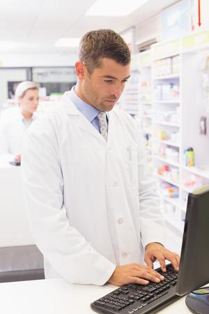 Pharmacist using the computer at the hospital pharmacy Stock Photo