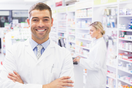 Smiling tpharmacist standing with arms crossed in the pharmacy Reklamní fotografie