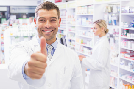Happy pharmacist holding his thumb at pharmacy