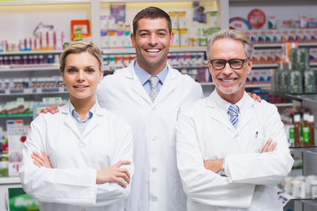 pharmacist: Team of pharmacists smiling at camera at the pharmacy