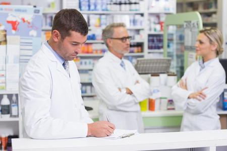 bata de laboratorio: Farmac�utico en bata de laboratorio escribir una receta en la farmacia Foto de archivo