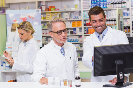 Team of pharmacists looking at computer at the hospital pharmacy photo