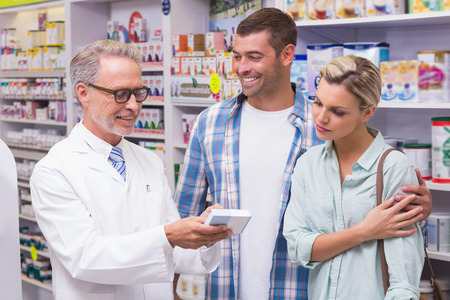 Apotheker en klanten glimlachen bij apotheek Stockfoto