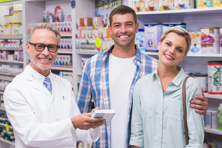 costumers: Pharmacist and costumers smiling looking at camera at pharmacy