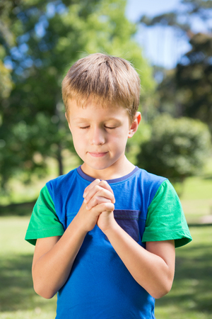 jehovah: Little boy saying his prayers on a sunny day Stock Photo