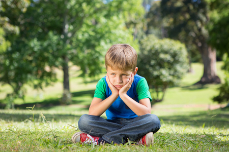 Little boy feeling sad in the park on a sunny day Stock Photo