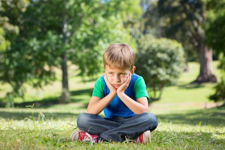 dia soleado: Niño pequeño sentirse triste en el parque en un día soleado