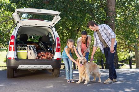 familias jovenes: Familia est� preparando para ir en viaje por carretera en un d�a soleado Foto de archivo